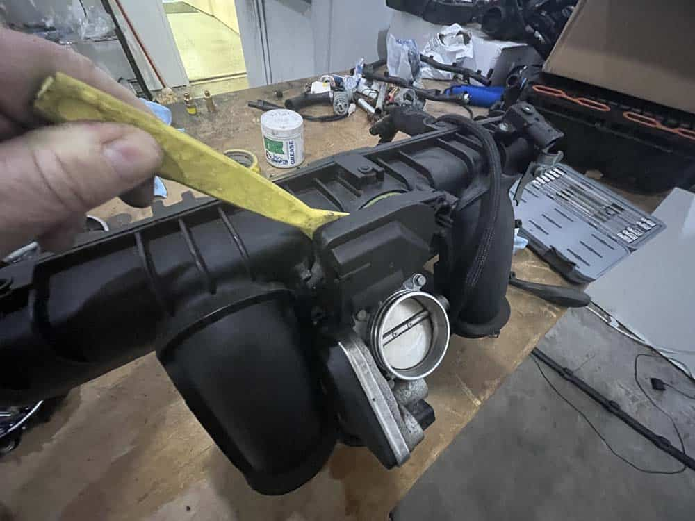 bmw n52 disa valve repair - pry the exterior DISA valve out of the manifold